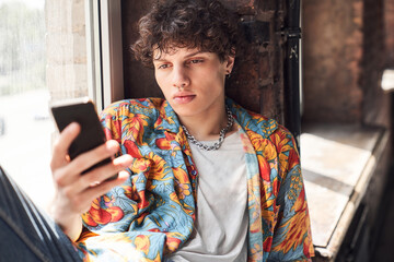 Fototapeta Handsome young man is using smartphone indoors obraz