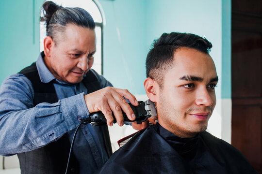 mexican man stylist cutting hair to a client in a barber shop in Mexico city