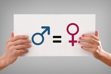Fototapeta Man and woman hand holding a poster with gender symbols