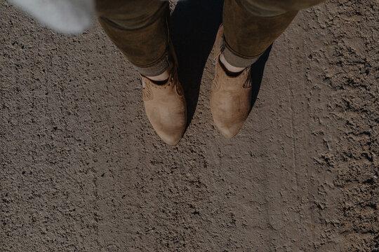 Woman in heels standing on road.