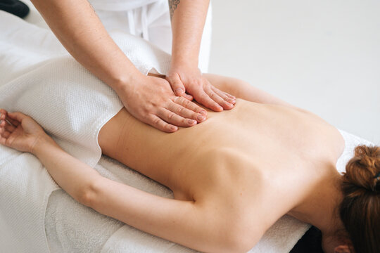 Top view of male masseur massaging lower back of young woman lying on massage table at light spa salon. Experienced chiropractor performs wellness treatments for lady with back pain.