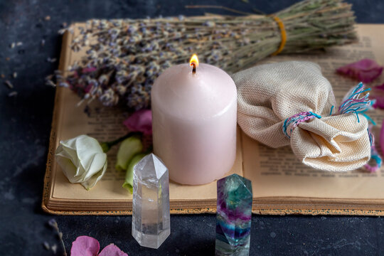 Magic still life with fluorite, quartz crystal and pink candle. Magic rocks for mystic ritual, witchcraft Wiccan or spiritual practice (healing). Meditation reiki. Ritual for love and chakra balance.