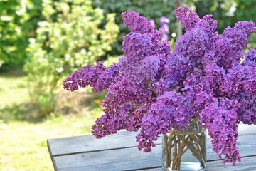 beautiful bouquet of purple lilac on a wooden table in garden