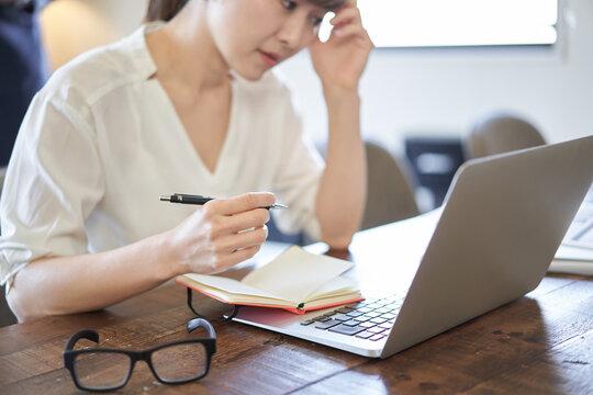パソコン作業での締切に悩むアジア人女性