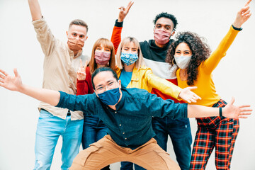 Multicultural people covered by protective face masks smiling at camera - New normal friendship...
