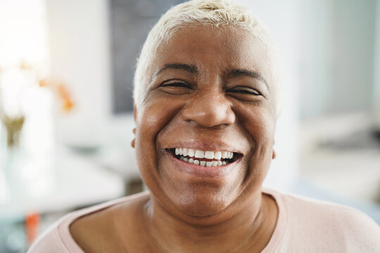 Portrait of happy senior african woman looking at camera indoors at home - Focus on face