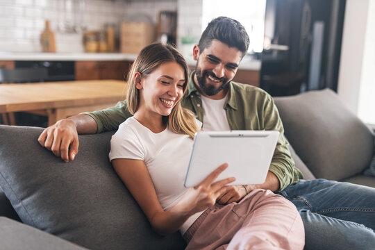 Excited modern couple smiling while looking at tablet