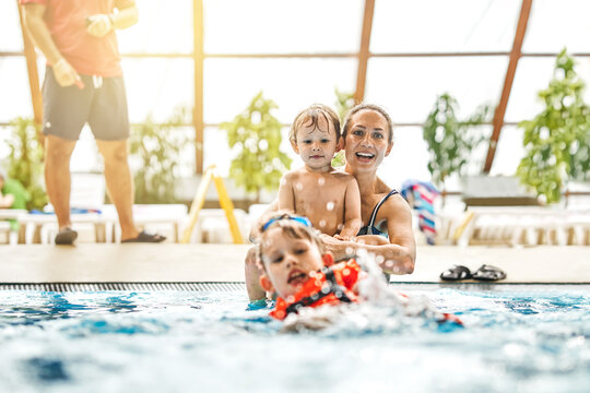 Joyful young mother with cute little sons has fun swimming and playing in large pool with clear water at city sports complex