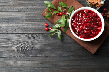 Flat lay composition with cranberry sauce on grey wooden table, space for text