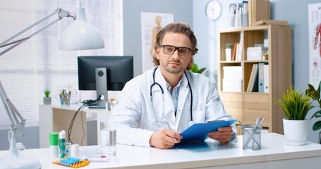 Portrait of middle-aged happy positive handsome Caucasian male doctor in glasses working in...