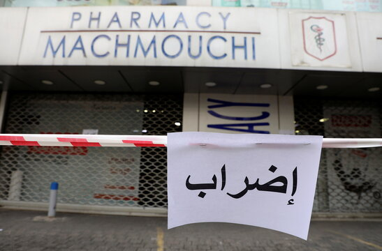 """A sign that reads """"on strike"""" is placed outside a closed pharmacy in Beirut"""