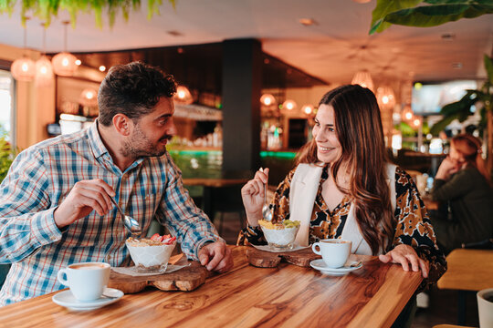 Young Caucasian couple having breakfast a Colombian coffee and a mixed fruit yogurt for a diet in a restaurant