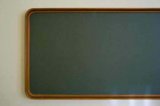 Vintage Chalkboard In Wooden Frame On White Wall