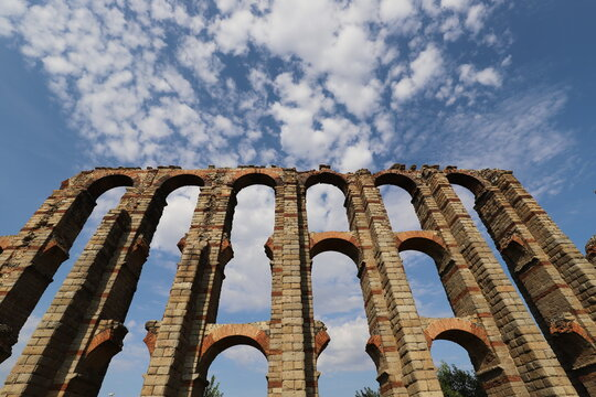 Low Angle View Of Old Ruin, Roman Aqueduct Against Blue Sky With White Clouds.