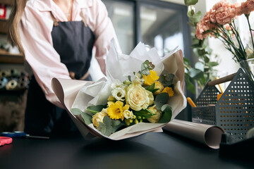 Obraz Portrait of successful modern florist wearing apron, creating beautiful bouquet of colorful different flowers in modern interior floral shop. Close up. - fototapety do salonu