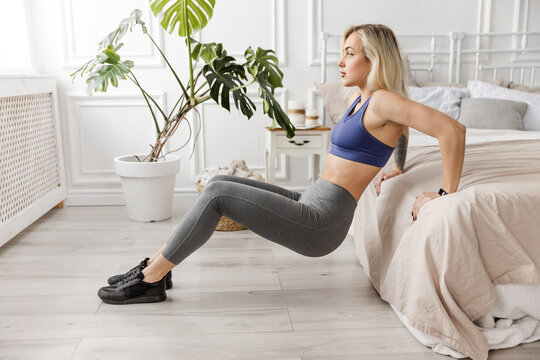 Sportive blonde girl in stylish sportswear working out at home, doing upward push-ups from the bed. Beautiful athletic woman keeping herself in shape, exercise, weight loss concept