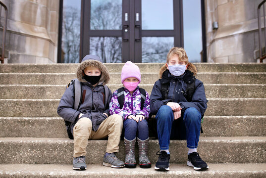 Little Kids Sitting on Steps to School Building with Protective Covid Masks