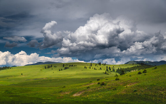 Clouds over green hills.