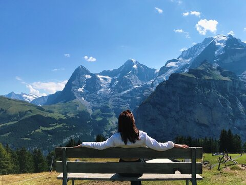 Rear View Of Woman Sitting On Bench Against Mountain Range