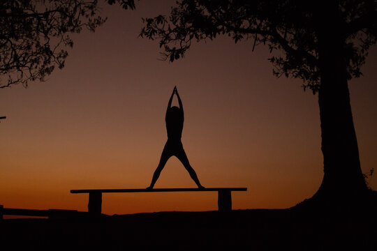 Silhouette Woman With Arms Raised Exercising On Bench Against Sky During Sunset