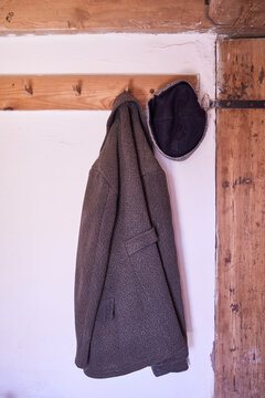 An Old Jacket And Cap Hanging On A Hanger