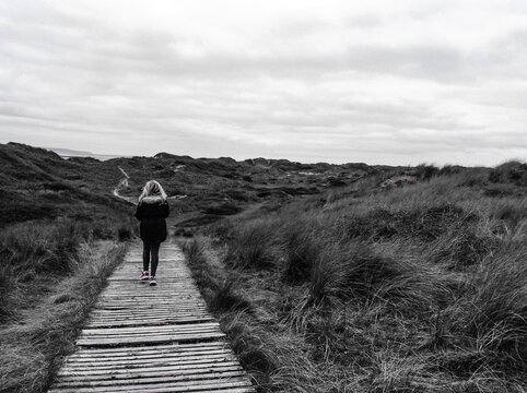 Rear View Of Woman Walking On A Wood Track Path.