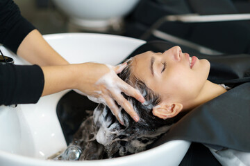 hairdresser is applying shampoo and massaging hair of a customer. Woman having her hair washed in a hairdressing salon..