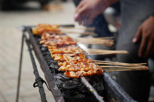 A Process Of Grilling A Few Ribs Of Blurry Chicken Satay Over Noisy Or Grainy Of Black Charcoal