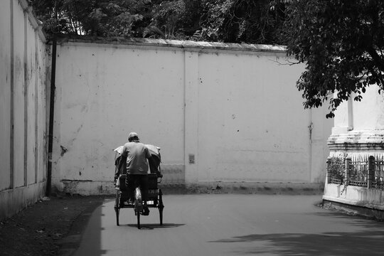 Rear View Of Man Riding Bicycle On Street