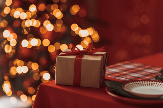 Close-up Of Gift Box On Table Against Illuminated Christmas Lights