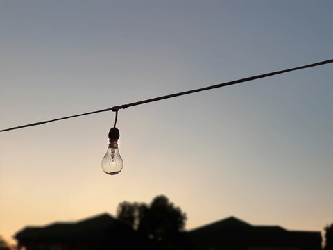 Close-up Hanging Incandescent Lamp During Sunset With Silhouette Of Houses And Trees On Background