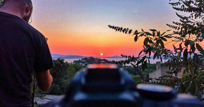 Man Photographing Orange Sky During Sunset