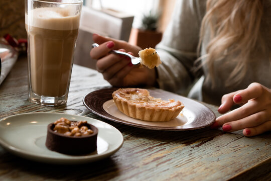 woman drinking latte and eating cake in coffee shop