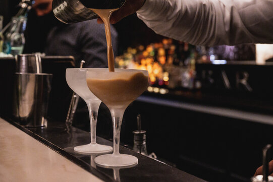 Cropped Hand Of Bartender Pouring Drink In Glass On Bar Counter