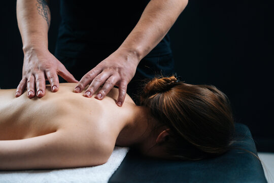 Close-up of chiropractor male massaging young woman lying on massage table, pushing on spine. Masseur sets the vertebrae in thoracic spine on black background. Concept of massage spa treatments.