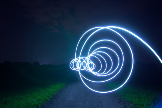 Light Trails On Road Amidst Field Against Sky At Night