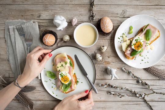 Easter breakfast with golden toasted Easter bread with butter and cheese and chives and basil with Easter decoration on light wooden background and delicious yellow sauce