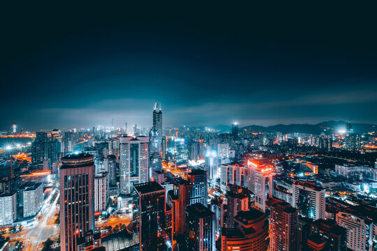 Illumminated Buildings In City At Night Against Sky