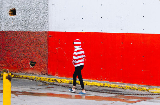Full Length Of Man Walking Against Red Wall