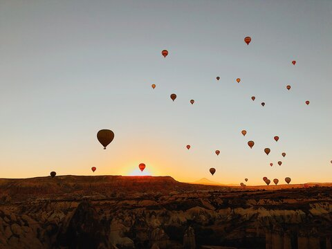 Hot Air Balloons Flying In Sky At Sunset