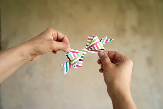 Hands Holding Gift Bow Made Of Colored Paper