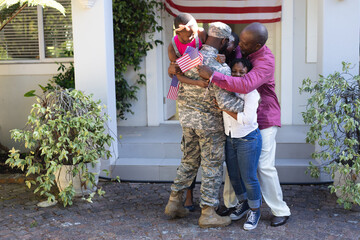 African american soldier father hugging wife, children and father in front of their house