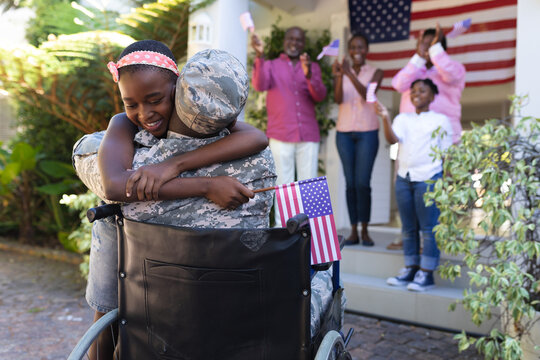 African american soldier father in wheelchair hugging daughter three generation family behind
