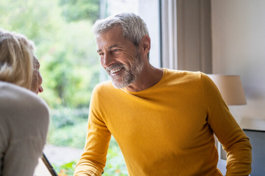 Smiling mature couple talking with each other at home