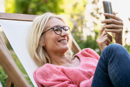 Smiling mature woman using smartphone while sitting on deckchair