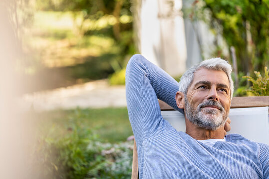 Thoughtful mature man with hands behind head sitting on deckchair