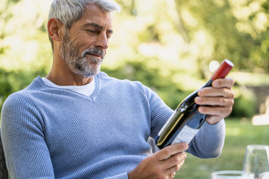 Mature man looking at wine bottle while sitting on chair