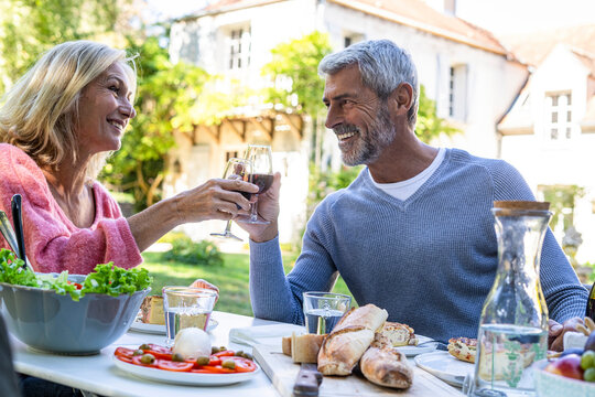 Smiling mature couple toasting wine glasses while sitting at table