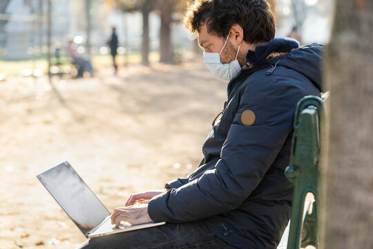 Side view of man wearing protective face mask using laptop in public park