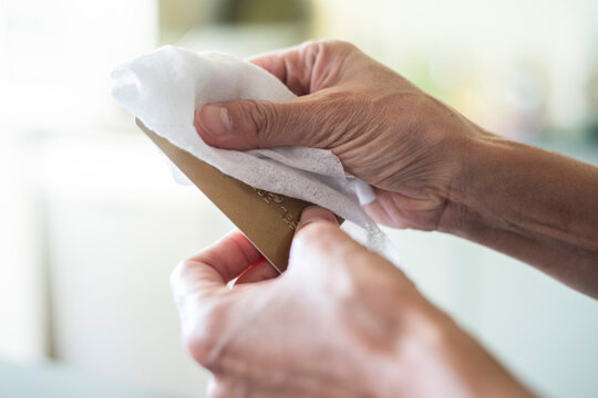 Close-up of woman's hands disinfecting credit card with wet wipe at home
